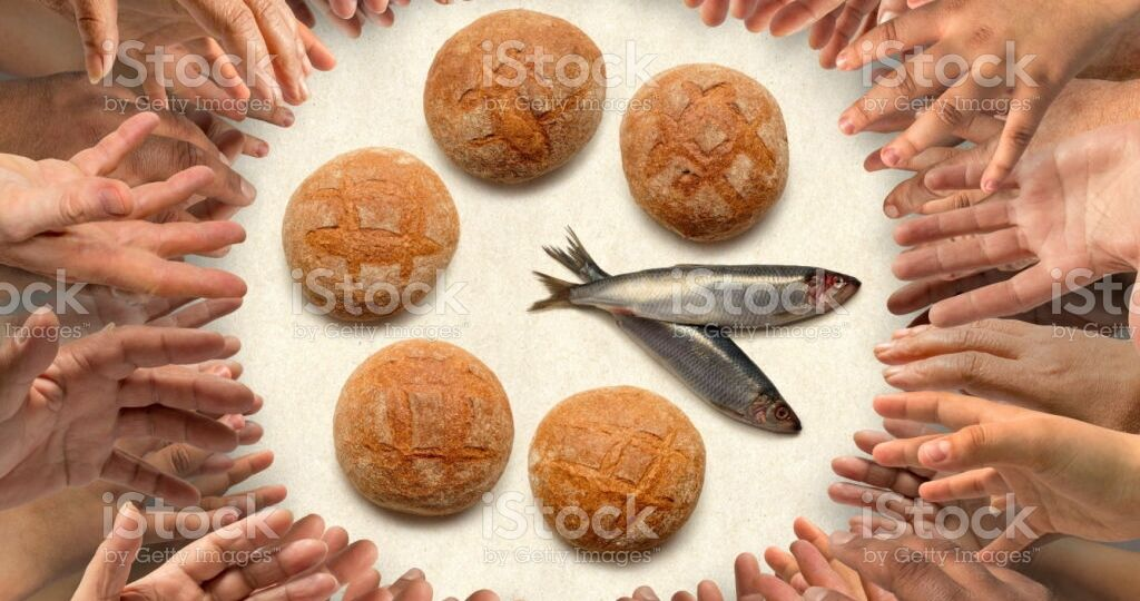 Many hands stretching around five small barley loaves and two small fish